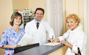 Doctor and his nurse receptionist greet a patient as she signs in and provides health insurance info.